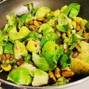 Brussels prouts and pistacchios cooking in a small pan